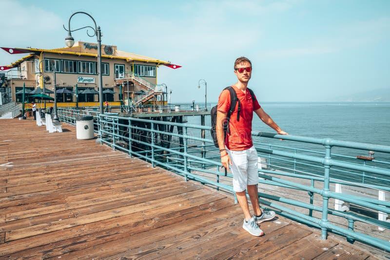 Человек исследуя пристань Санта-Моника около пляжа Венеции стоковое изображение