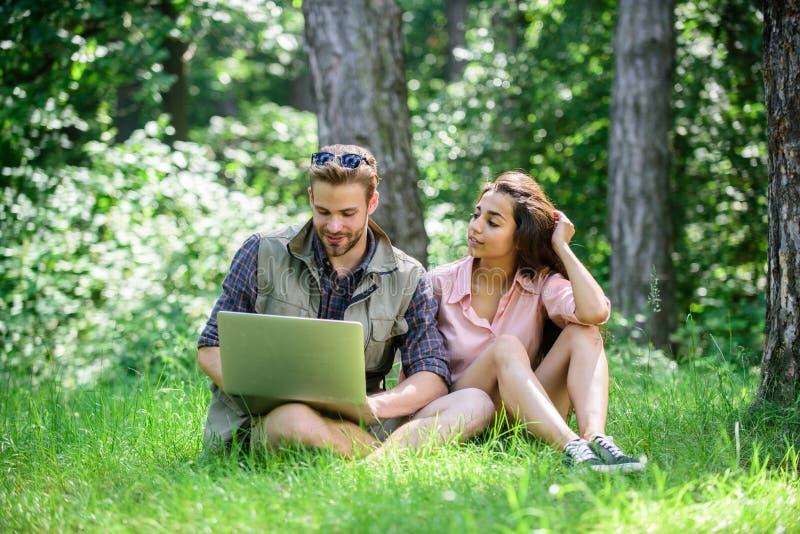 Человек и девушка работая с компьтер-книжкой на зеленом луге Независимая возможность Современные технологии дают возможность рабо стоковое изображение