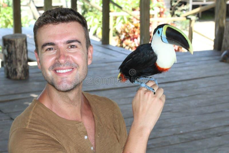 Человек и его одомашниванная toucan птица стоковые изображения rf