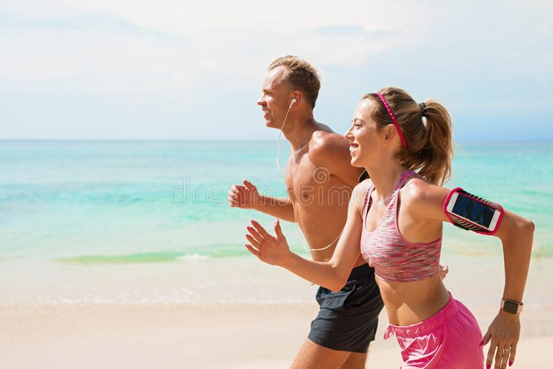 Человек и женщина бежать на пляже совместно стоковые фотографии rf