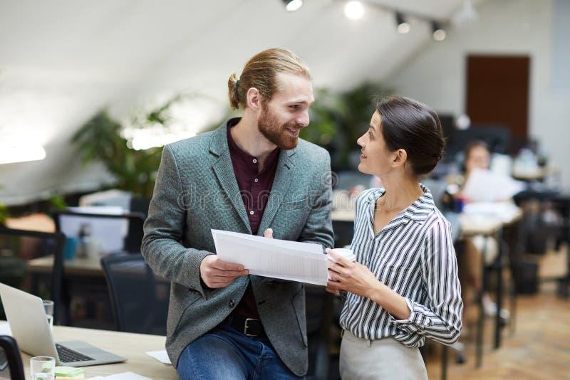 Человек и женщина беседуя в офисе стоковое фото rf