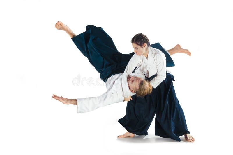 Человек и женщина воюя на тренировке айкидо в школе боевых искусств стоковое изображение