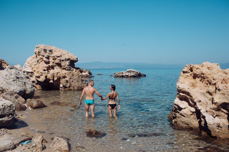 Человек и женщина в стойках бикини в море между рифом на солнечный день Пары в стойках любов в воде около камня или утеса дальше стоковое изображение rf