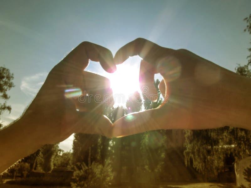 Человек и женщина делают сердце вокруг солнца с их руками Мужчина и женская рука в лучах и слепимости солнца делают форму стоковое изображение