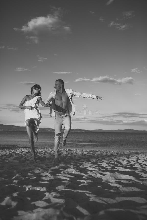 Человек и женщина держат руки, пары счастливые на каникулах Пары в влюбленности стоят на пляже, seashore Пары в идти влюбленности стоковая фотография rf