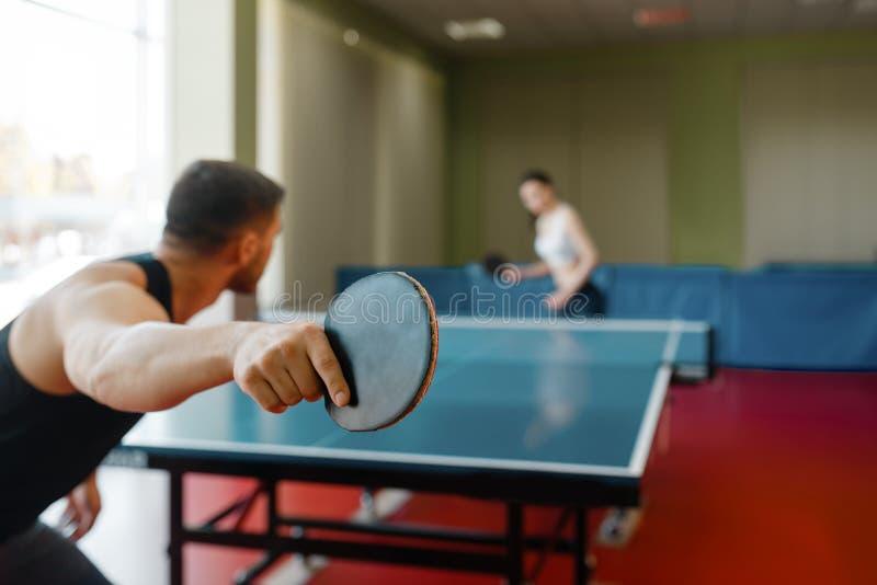 Человек и женщина играя пингпонг, фокус на ракетке стоковое фото