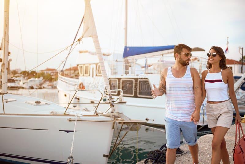 Человек и женщина идя на яхты на доке стоковая фотография