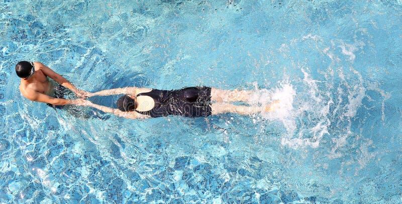 Человек и женщина ослабляя в бассейне стоковые изображения