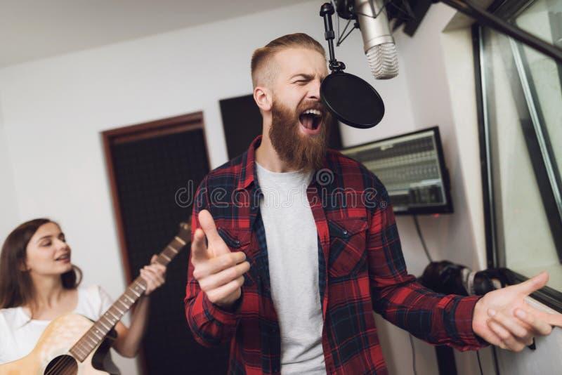 Человек и женщина поют песню на студии звукозаписи стоковая фотография rf