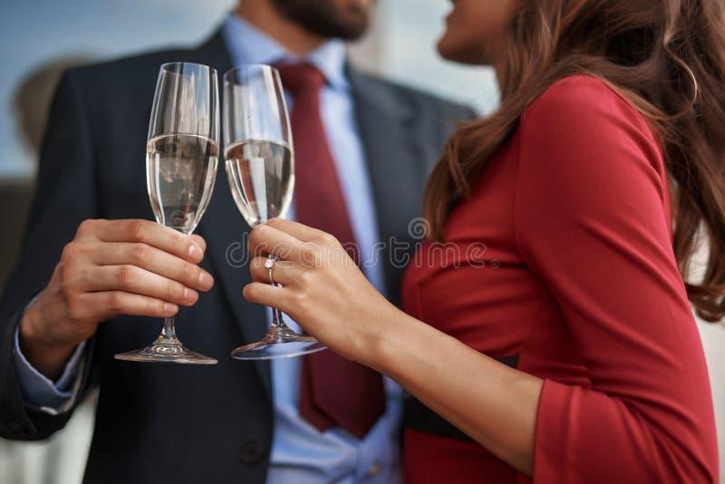 Человек и женщина празднуя со стеклами шампанского на открытом воздухе стоковое изображение