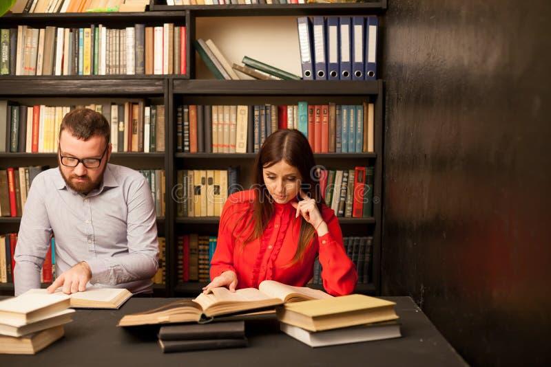 Человек и женщина прочитали книги в библиотеке подготавливают для экзамена стоковые изображения rf