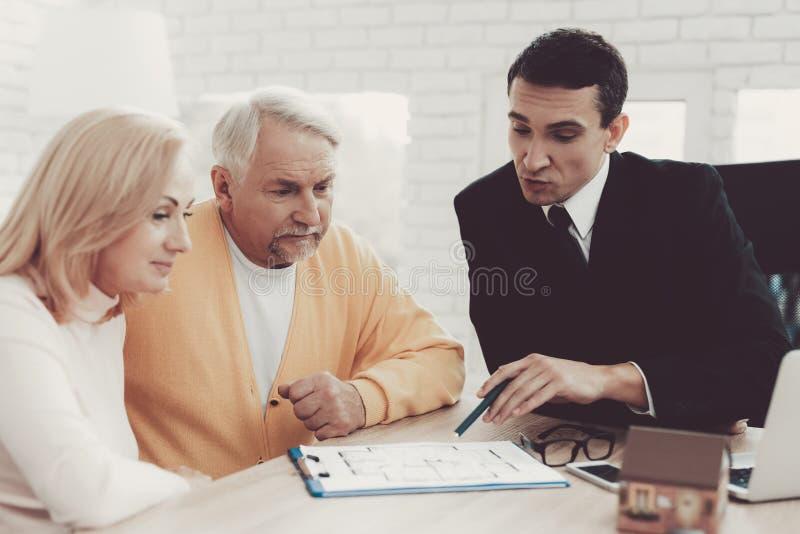 Человек и женщина советуя с с риэлтором в офисе стоковое изображение rf