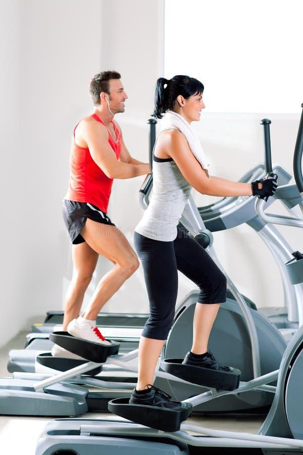 Человек и женщина с эллиптическим перекрестным тренером на гимнастике стоковые изображения rf