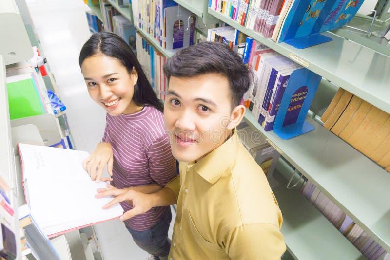 Человек и женщина читают и говорят открытую книгу на книжных полках стоковая фотография rf