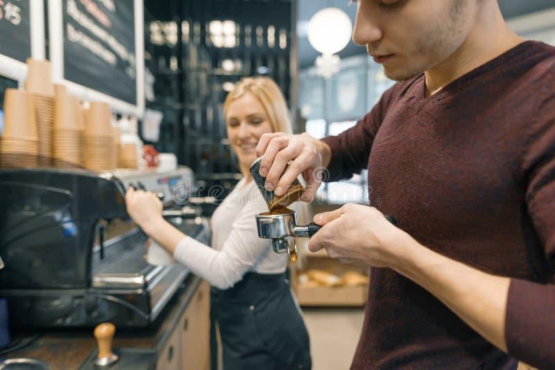 Человек и женщина Barista делая кофе, пару молодых людей работая в кофейне стоковые фото