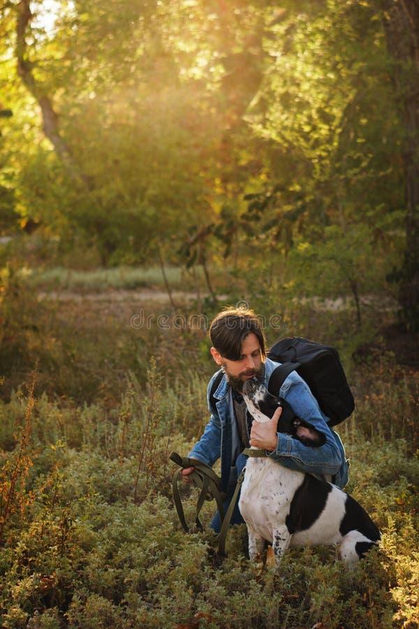 Человек и собака в парке осени стоковое изображение