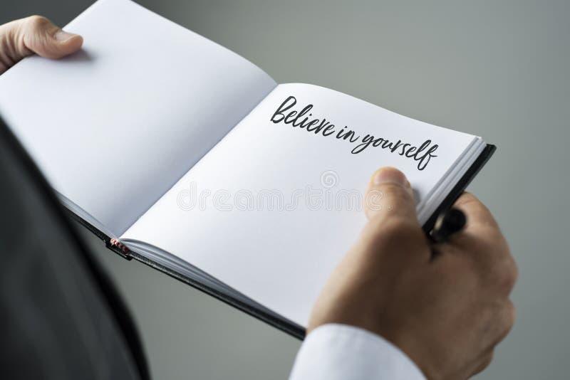 Человек и тетрадь с текстом верят в себе стоковые изображения