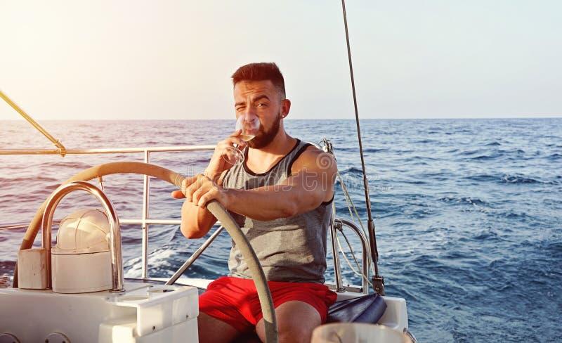 Человек капитана плавая на яхте с бокалом вина Досуг лета стоковые фото