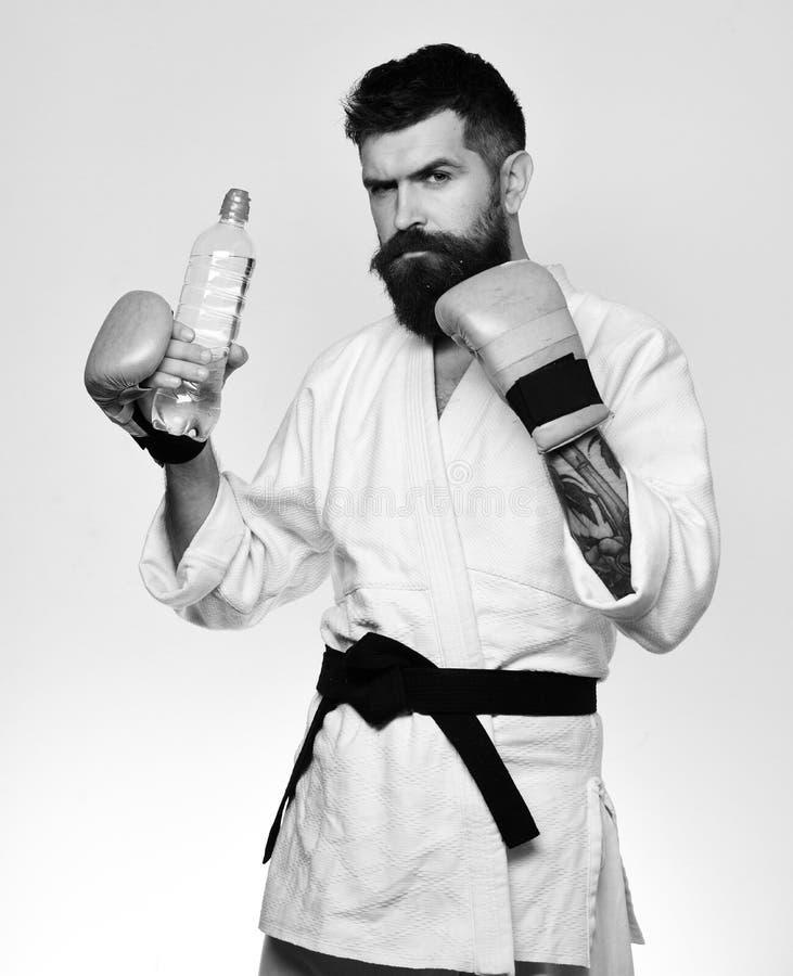 Человек карате с серьезной стороной в перчатках бокса держит бутылку с водой Oriental резвится концепция Пить мастера боя стоковые изображения rf