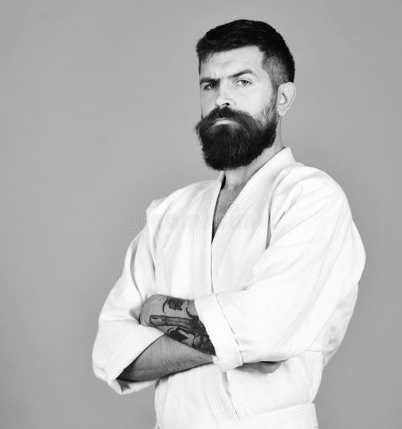 Человек карате с строгой стороной в форме Человек с бородой в белом кимоно на красной предпосылке Мастер Тхэквондо держит оружия стоковые изображения