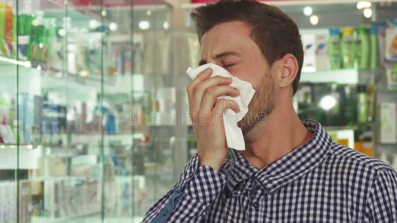 Человек кашляя и чихая в аптеке стоковые фото