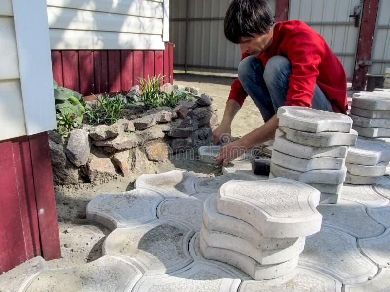 Человек кладет вымощая плиты во дворе  его дома Взрослый парень в случайных одеждах устанавливает бетонную плиту в сухой цемент-п стоковая фотография