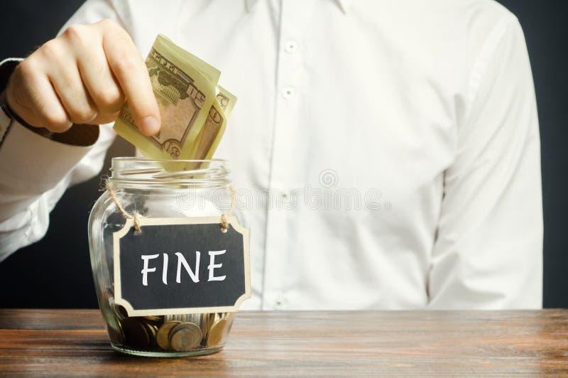 Человек кладет доллары в стеклянный опарник со штрафом слова Сохраняя деньги и оплачивать штраф Наказание для преступления и обид стоковая фотография