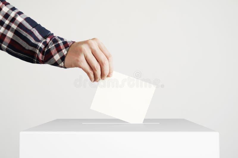 Человек кладя голосование в голосуя коробку стоковые изображения rf