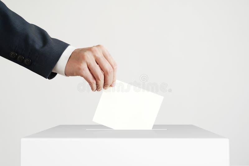 Человек кладя голосование в голосуя коробку стоковое фото