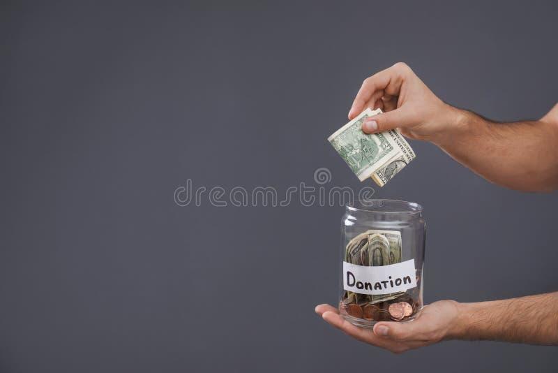 Человек кладя деньги в опарник с ПОЖЕРТВОВАНИЕМ ярлыка на серую предпосылку, крупный план стоковая фотография rf