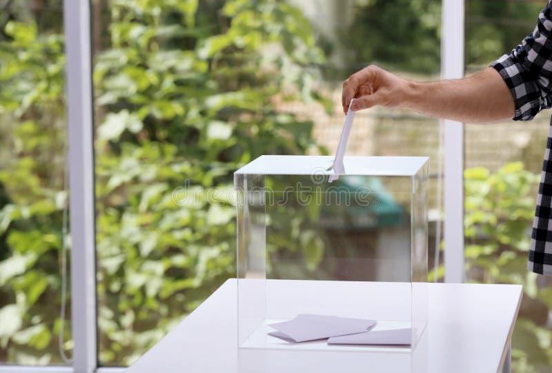Человек кладя его голосование в урну для избирательных бюллетеней на избирательном участке, крупном плане стоковые изображения rf