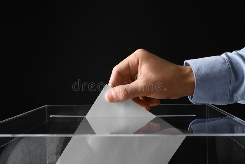 Человек кладя его голосование в урну для избирательных бюллетеней на черное, крупный план стоковые изображения