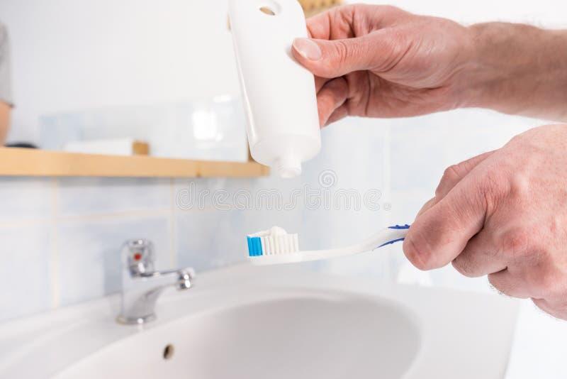 Человек кладя зубную пасту на зубную щетку стоковое фото
