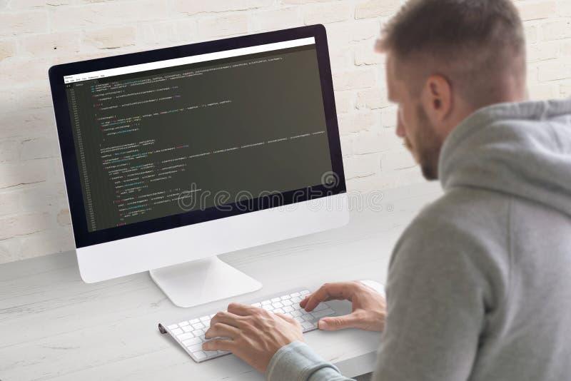 Человек кодируя приложение на компьютере Сцена конца-вверх Чистый стол офиса с кирпичной стеной в предпосылке стоковая фотография rf