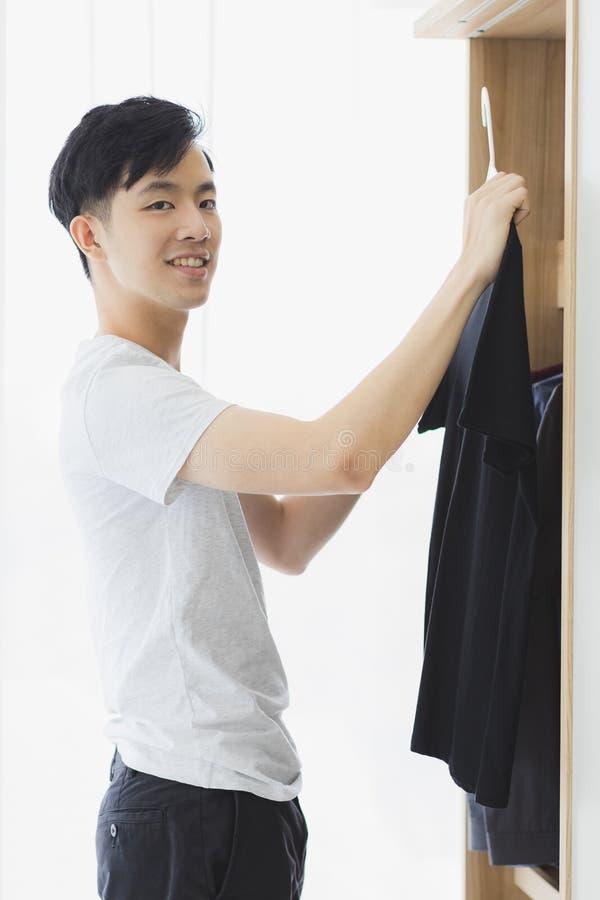 Человек комплектует вверх черную футболку от шкафа стоковая фотография