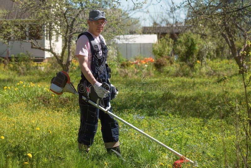 Человек косит траву на газонокосилках Прозодежды и инструменты стоковое изображение