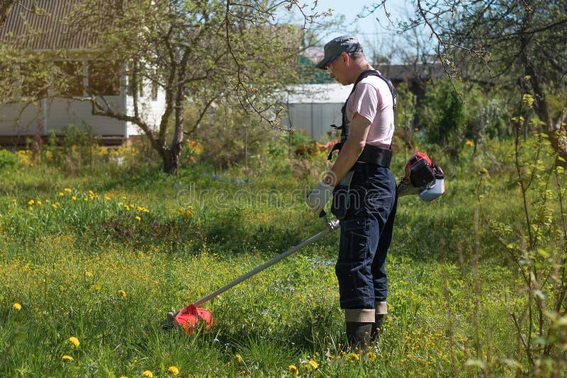 Человек косит траву на газонокосилках Прозодежды и инструменты стоковое фото
