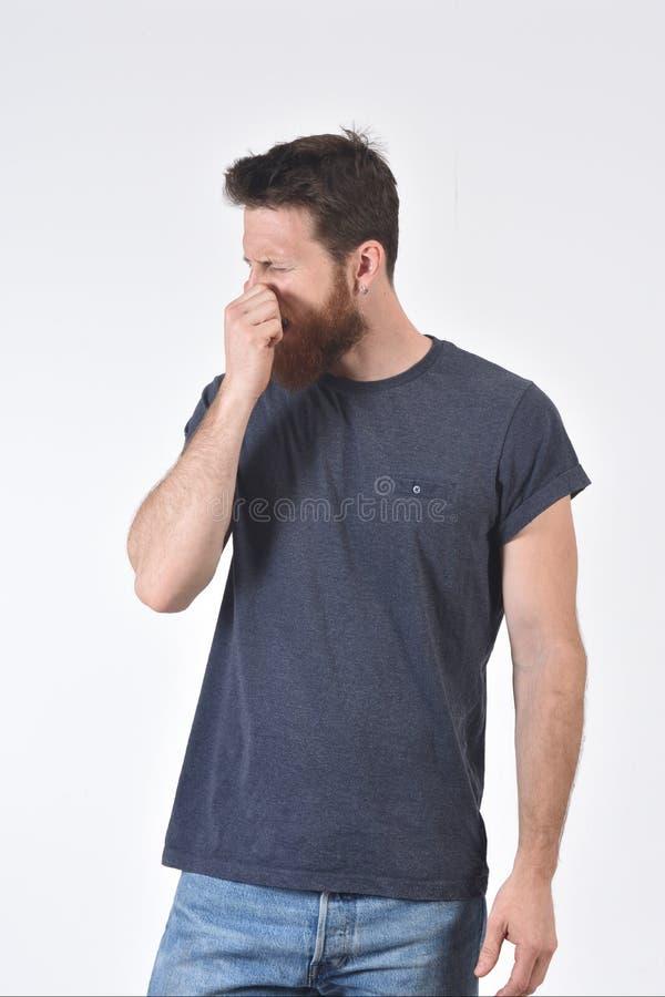 Человек который покрывает его нос с его пальцами потому что он делает запах плохой стоковые фотографии rf
