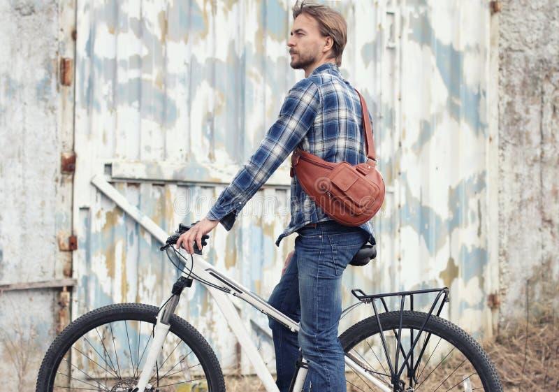 Человек красивого битника бородатый с современной кожаной сумкой на велосипеде стоковая фотография