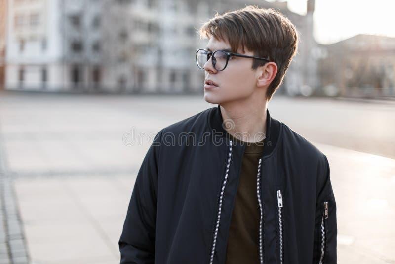 Человек красивого хипстера молодой в стильных стеклах с модным стилем причесок в стильном outerwear на улице в городе стоковые изображения