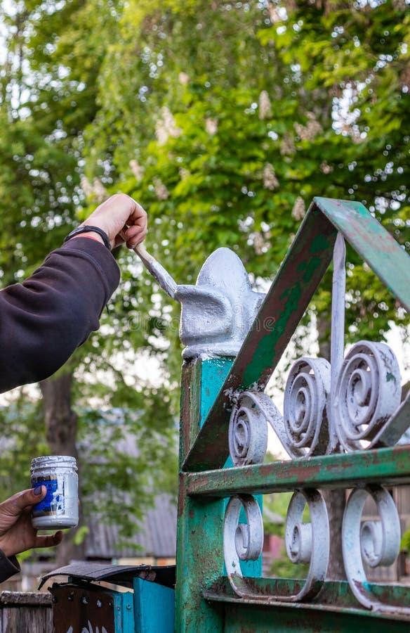Человек красит дверь с краской для защиты продукта от корозии стоковые изображения rf
