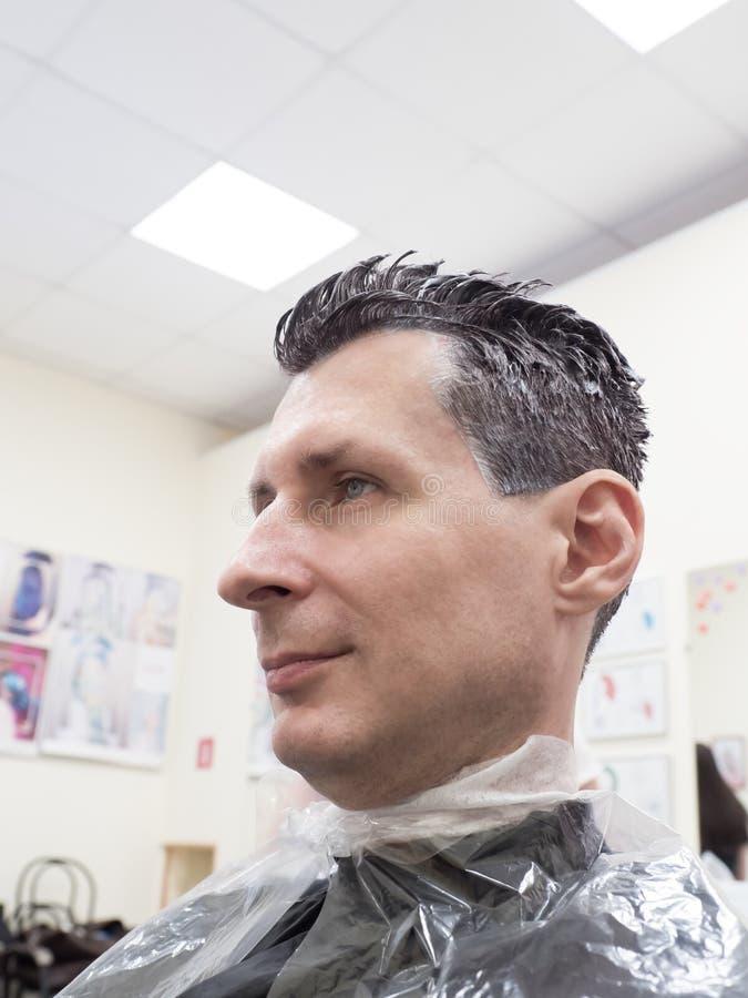 Человек красит его волосы в салоне красоты стоковые фотографии rf