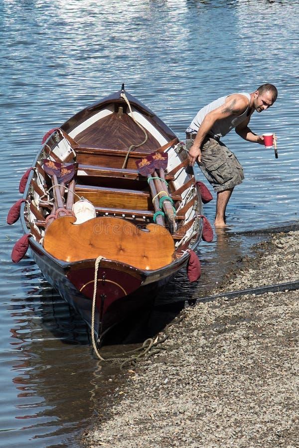 Человек крася весельную лодку стоковое фото rf