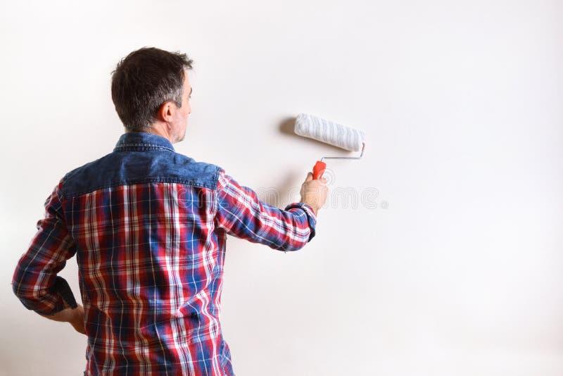 Человек крася стену его дома в белизне стоковые фото