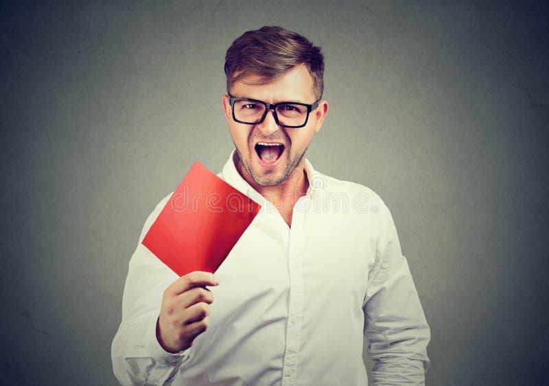 Человек кричащий и показывая красную карточку стоковое изображение rf