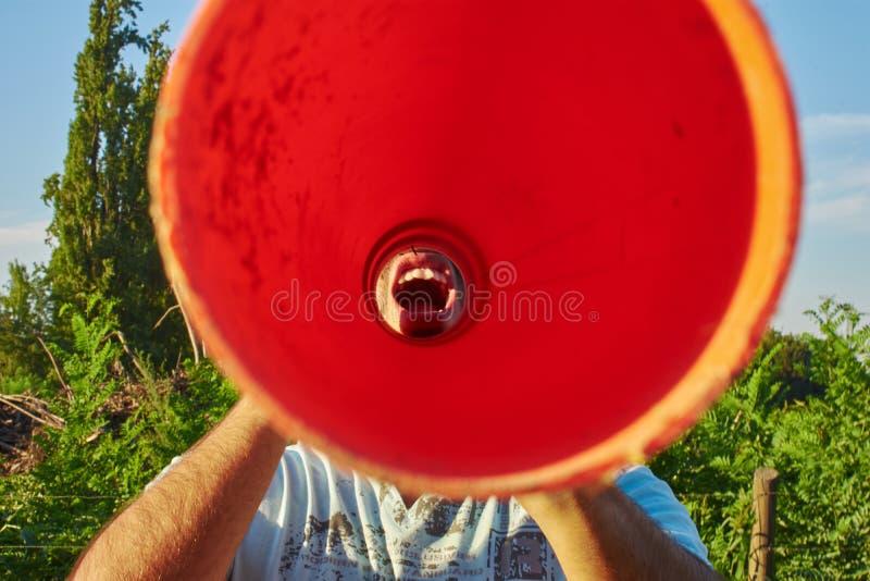Человек крича через оранжевую трубку стоковое изображение rf