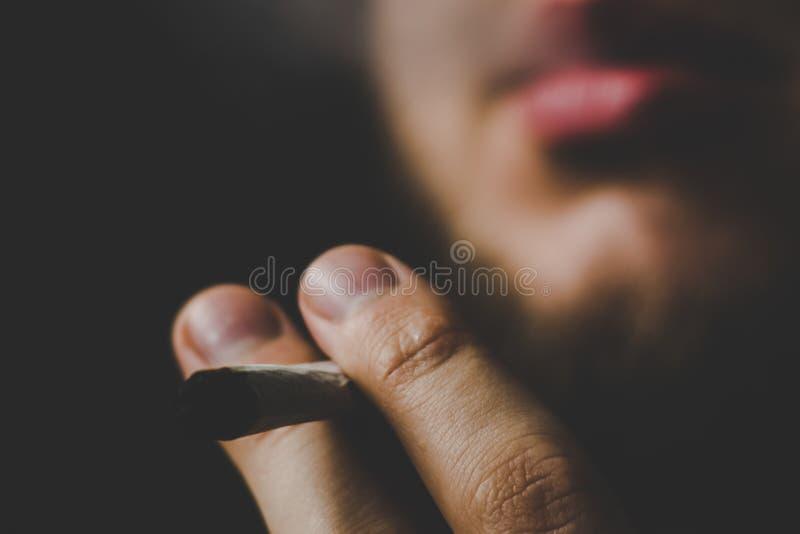 Человек курит засоритель конопли, соединение и лихтер в его руках дым предпосылки черный Концепции медицинской марихуаны стоковые фотографии rf
