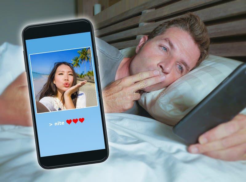 Человек лежа на кровати посылая текст поцелуя спокойной ночи при мобильный телефон имея звонок интернета видео- с азиатской китай стоковые фотографии rf