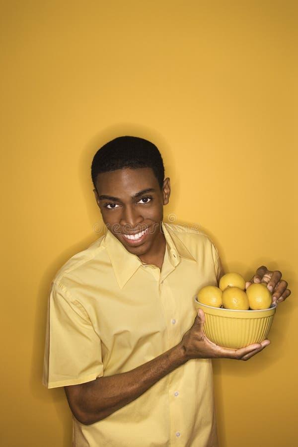 человек лимонов удерживания шара афроамериканца стоковое изображение