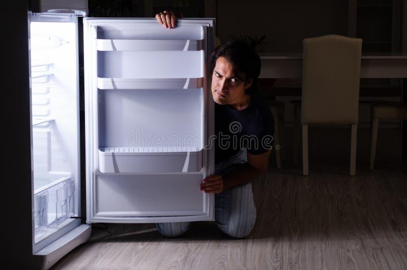 Человек ломая диету вечером около холодильника стоковое изображение rf